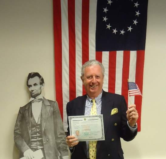 Stuart Kennedy holding up his Citizenship and American flag